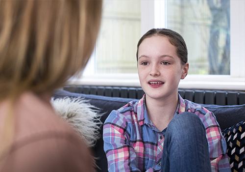Girl smiling as she is talking to a parent